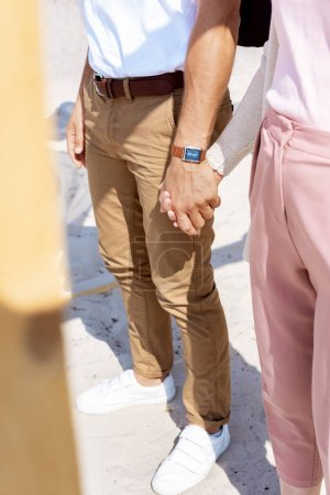 partial view of couple holding hands while walking on sandy beach