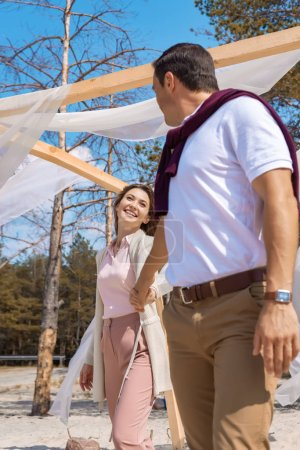 happy couple holding hands on sandy beach with white curtain lace decoration