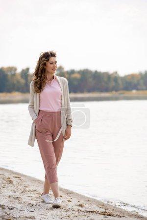 attractive pensive woman walking on sandy beach alone