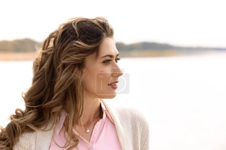 side view of thoughtful woman looking away with sea on background