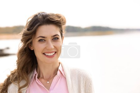 portrait of beautiful smiling woman with looking at camera river on background