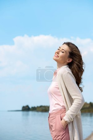 Photo for Side view of beautiful smiling woman with river on background - Royalty Free Image