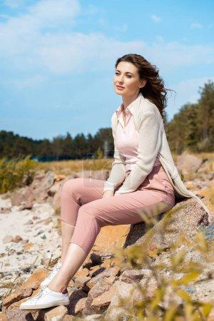 attractive pensive woman resting on rocks on sandy beach