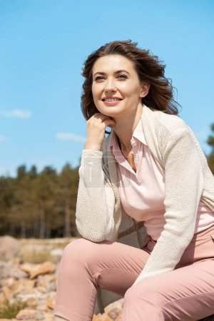 portrait of attractive woman resting on rocks on sandy beach