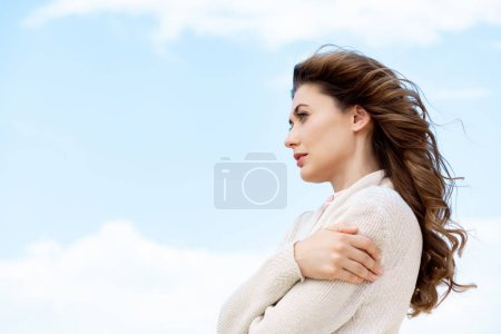 side view of beautiful pensive woman with blue cloudy sky on background