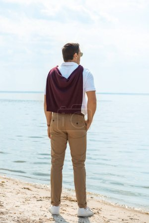 Photo for Back view of stylish man standing on sandy riverbank alone - Royalty Free Image
