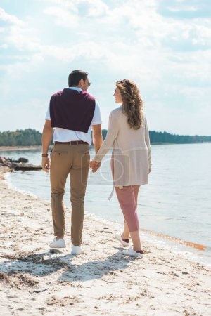 romantic couple holding hands while walking on sandy riverside