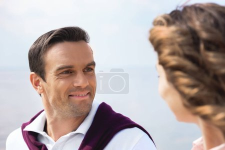 portrait of smiling couple looking at each other with blue sky on background
