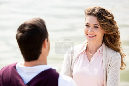 happy couple looking at each other with sea on background
