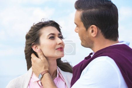 side view of romantic couple looking at each other with blue sky on backdrop