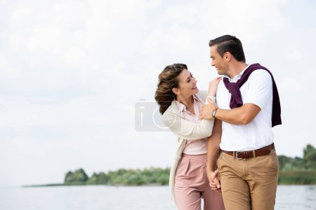 portrait of happy couple looking at each other on beach