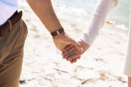 Photo pour Vue partielle du couple tenant la main en marchant sur une plage de sable - image libre de droit