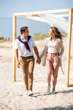 happy couple holding hands while walking on sandy beach