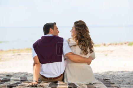 Photo pour Vue arrière du couple romantique reposant sur une couverture sur une plage de sable - image libre de droit