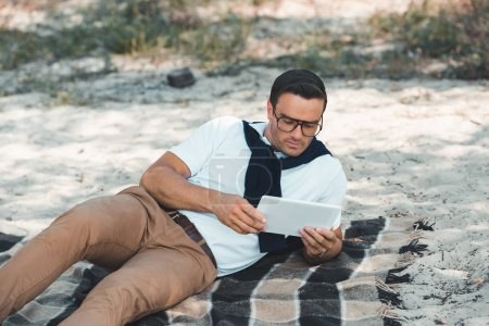 stylish man using tablet while resting on blanket on sandy ground