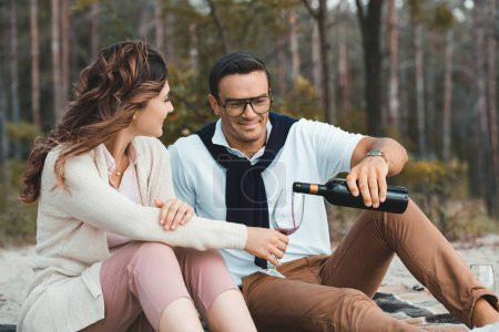 Photo for Man pouring red wine into glass while resting together with wife on sandy beach - Royalty Free Image