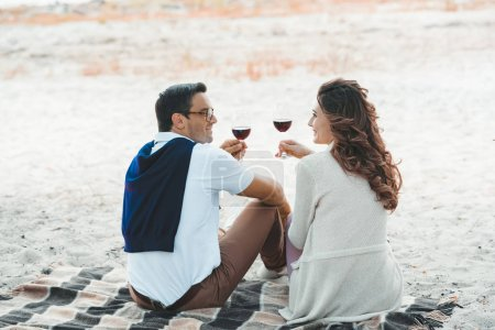 rear view of couple with glasses of red wine resting on blanket on sandy beach
