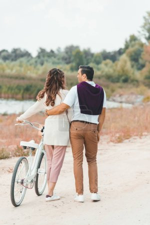back view of couple with retro bicycle on sandy beach
