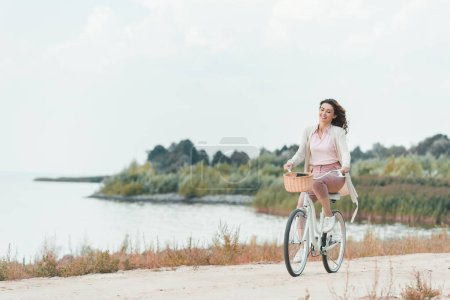 smiling woman riding retro bicycle on sandy riverside