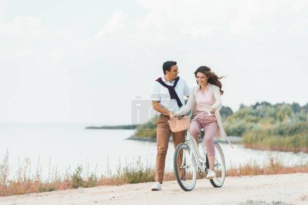 man helping wife ride retro bicycle on sandy riverside