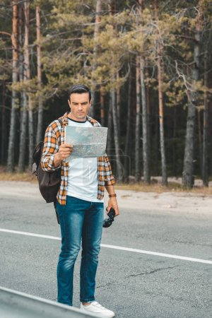 tourist with binoculars looking at map while standing on empty road