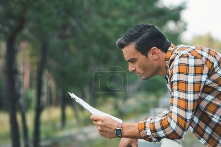 Photo for Side view of focused tourist looking at map - Royalty Free Image