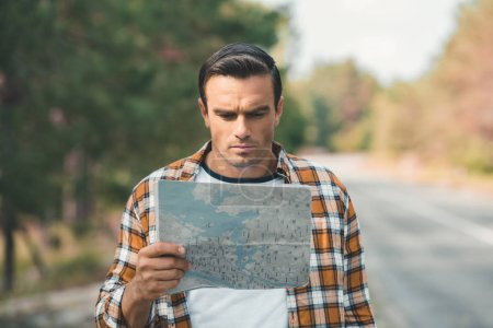 portrait of concentrated tourist looking at map while standing on road