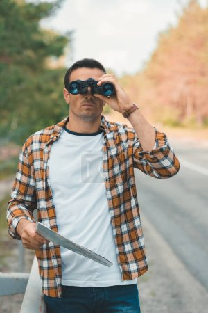 Photo for Portrait of tourist with map and binoculars standing on road - Royalty Free Image