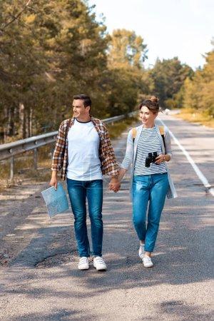 couple avec sacs à dos, main dans la main tout en voyageant ensemble