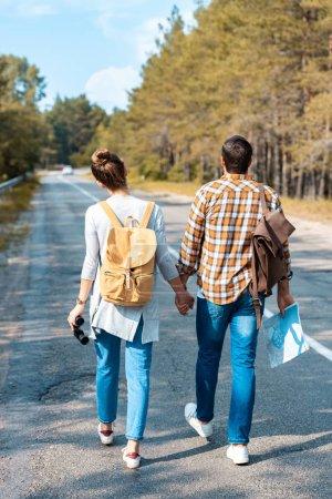 Photo pour Vue arrière des touristes avec des sacs à dos tenant la main tout en marchant sur la route ensemble - image libre de droit
