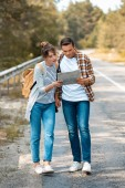 tourists with map looking for destination while standing on empty road