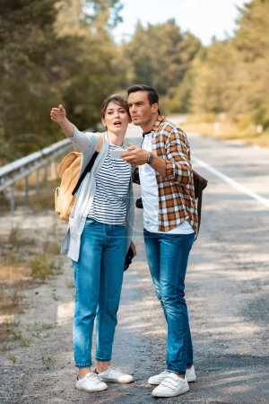 tourists with smartphone looking for destination while standing on empty road