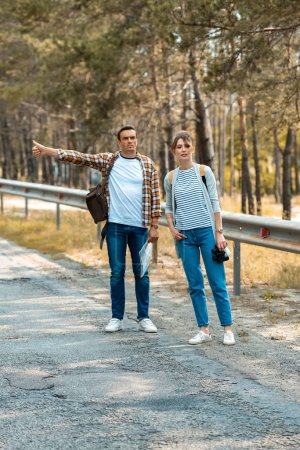 couple with backpacks and map hitchhiking on road together