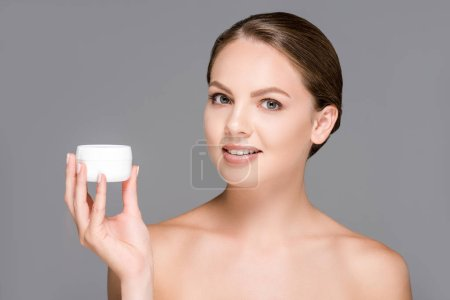 portrait of beautiful young woman holding face cream isolated on grey