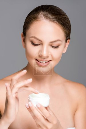 portrait of beautiful smiling woman with face cream isolated on grey
