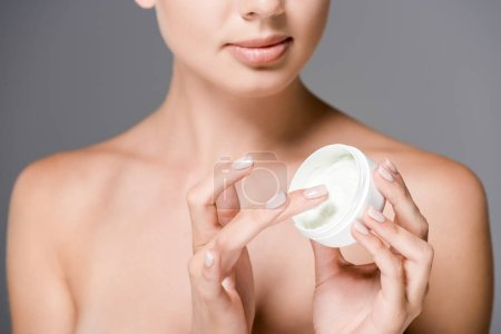 partial view of woman with face cream isolated on grey