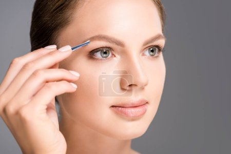Photo for Portrait of young woman plucking eyebrows with tweezers isolated on grey - Royalty Free Image