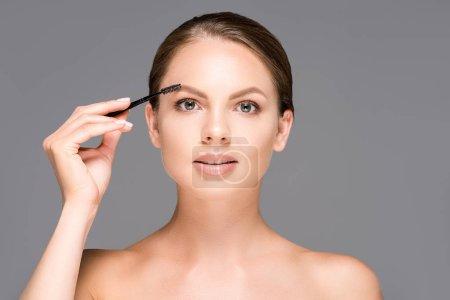 Photo pour Portrait de belle femme avec pinceau de maquillage pour sourcils isolé sur gris - image libre de droit