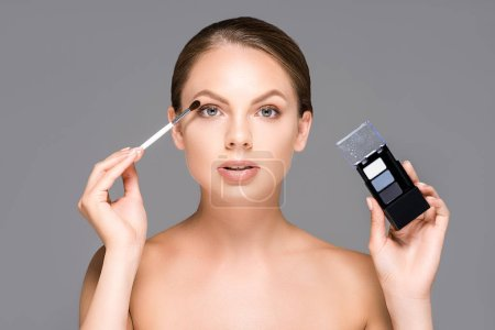 portrait of attractive woman with eyeshadows and makeup brush isolated on grey