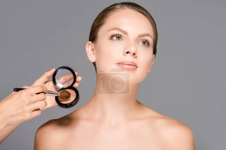 partial view of beautiful woman and makeup artist with blush and brush isolated on grey