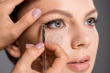 Photo pour Plan recadré de maquilleur appliquant un eye-liner sur le visage des modèles sur fond gris - image libre de droit