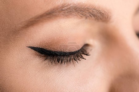 partial view of woman with black eyeliner on eyelid