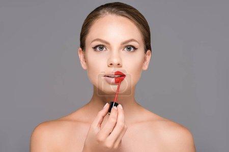 Photo pour Portrait de belle jeune femme aux épaules nues appliquant rouge à lèvres isolé sur gris - image libre de droit