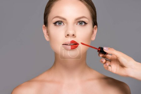 partial view of makeup artist applying red lipstick on models lips isolated on grey