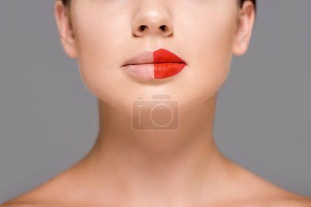 cropped shot of woman with red lipstick on half of mouth isolated on grey
