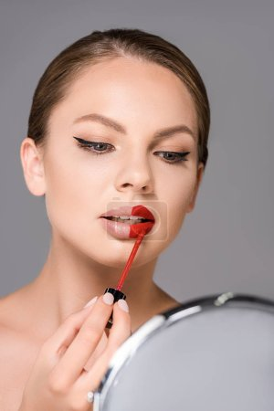 portrait of attractive woman looking at mirror and applying red lipstick isolated on grey