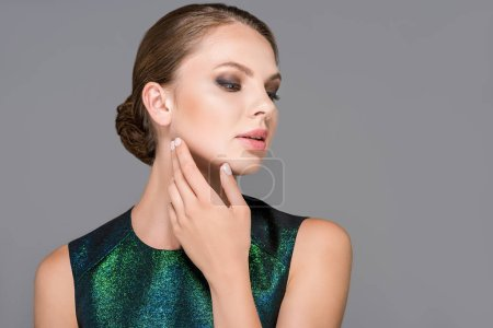 portrait of elegant model in green clothing isolated on grey