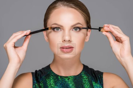 portrait of elegant woman with mascara and makeup brush for eyeshadows isolated on grey