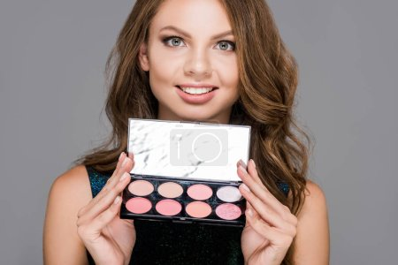 portrait of smiling woman with eyeshadows palette isolated on grey
