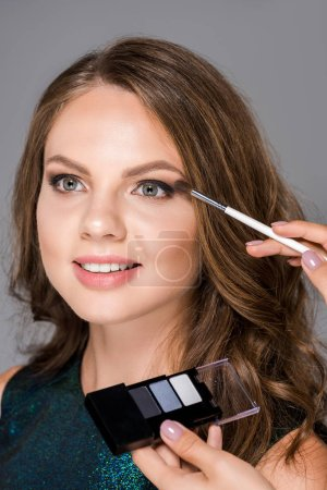 cropped shot of makeup artist applying eyeshadows on models face isolated on grey